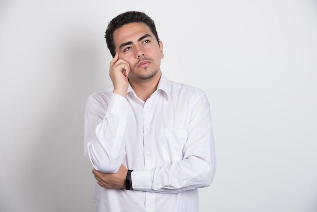 Giovane imprenditore pensando intensamente su sfondo bianco. Foto Gratuite