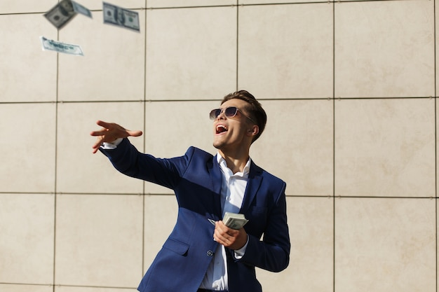 Young businessman throughs around dollars and dances on the street Free Photo