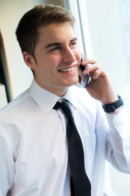 オフィスで彼の携帯電話を使用している若い実業家。 無料写真