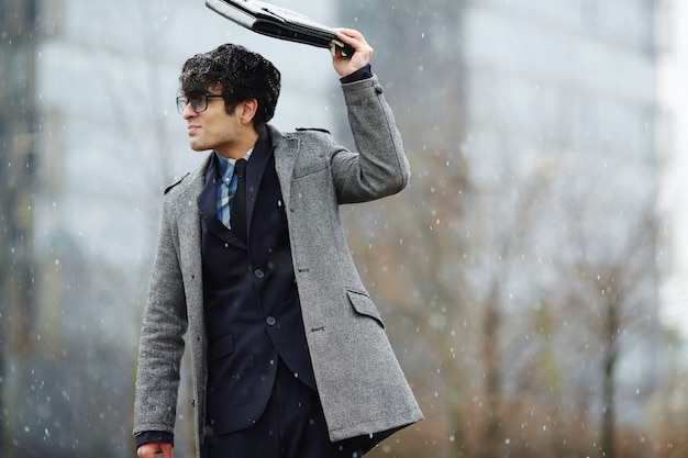 Young businessman walking in snowfall Free Photo