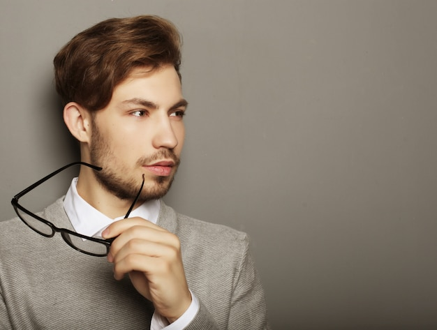 Young businessman with eyeglasses, looking at the camera against Premium Photo