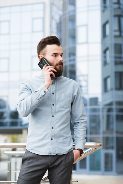 Young businessman with hands in his pocket talking on mobile phone Free Photo