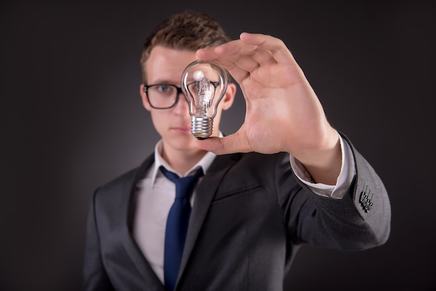 Young businessman with light bulb in idea concept Premium Photo