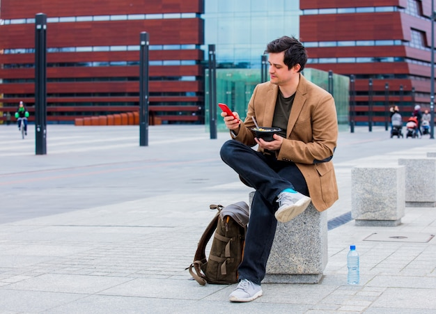 Young businessman with salad and mobile phone at urban city outdoor. Premium Photo