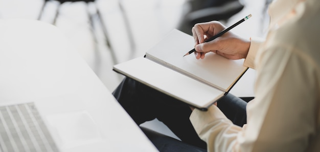 Young businessman working on his project while writing on notebook Premium Photo
