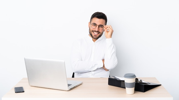 Young businessman in a workplace with glasses and happy Premium Photo