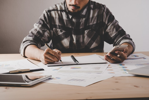 Young businessman writes in a notebook while working analysis business data in office. Free Photo
