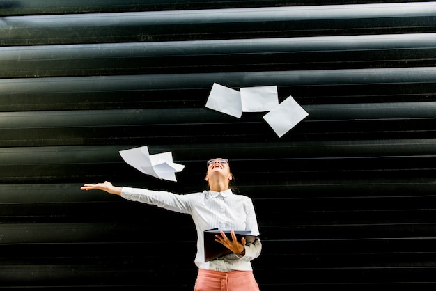 Young businesswoman in business clothing throwing up paper documents outdoor Premium Photo