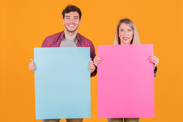Young businesswoman and businessman holding blue and pink placard against an orange background Free Photo