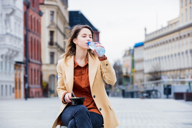 Young businesswoman eating salad and drinking water Premium Photo