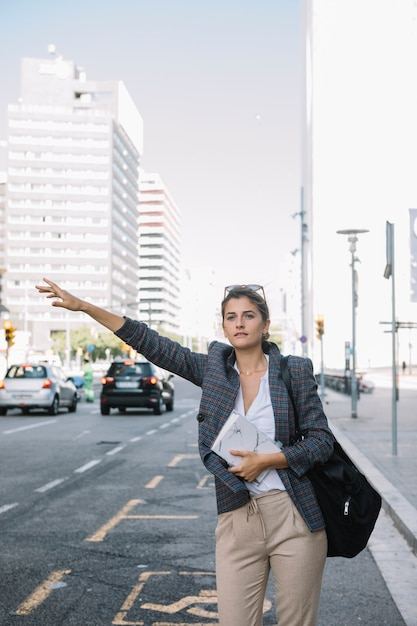 Young businesswoman hailing taxi on city street Free Photo