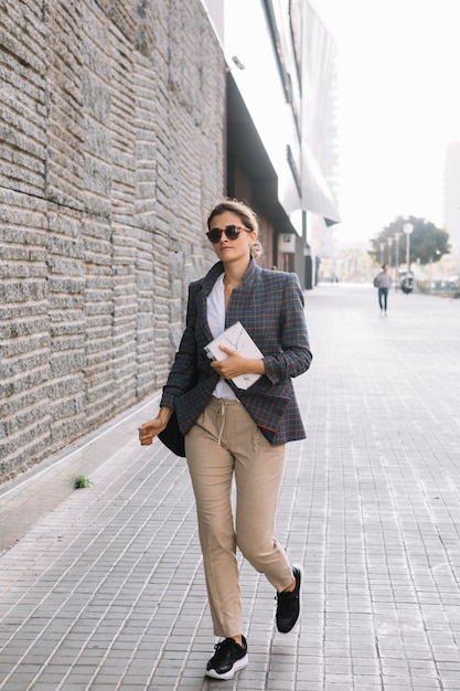 Young businesswoman holding diary in hand walking on street Free Photo