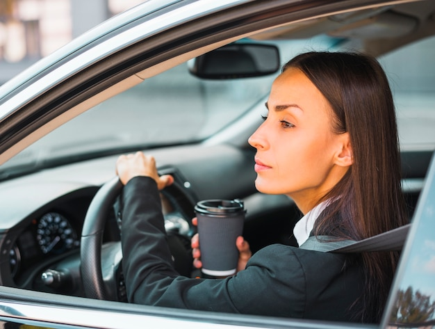 車を運転する使い捨てのコーヒーカップを保持している若い実業家 無料写真