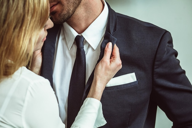 Young businesswoman holding jacket collar of businessman. flirting couple of unrecognizable caucasian people. passionate love affair in office workplace. close up shot Premium Photo