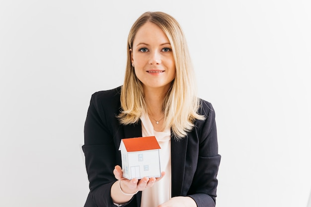 Young businesswoman holding miniature house model over white background Free Photo