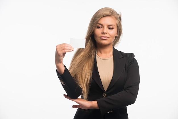 顧客の名刺をチェックする黒いスーツを着た若い実業家。 無料写真