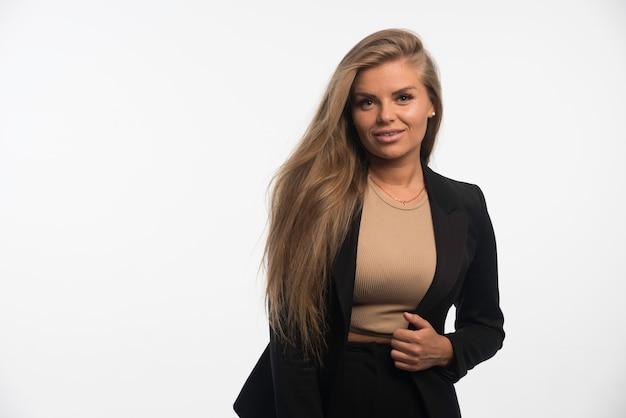 黒のスーツを着た若い実業家は自信を持ってプロフェッショナルに見えます。 無料写真