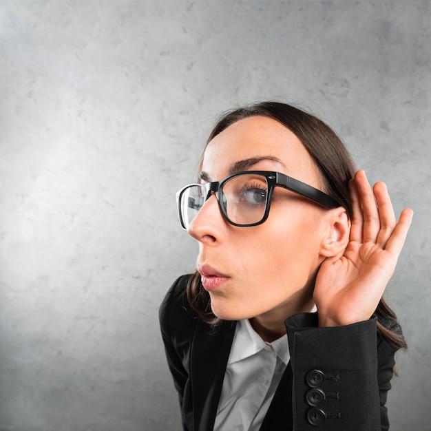 Молодая коммерсантка слушая с ее рукой на ухе против серой предпосылки Premium Фотографии