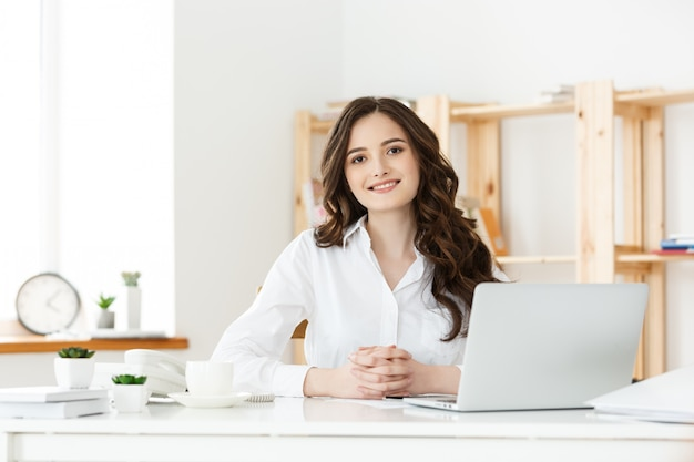 Young businesswoman or secretary sitting at desk and working. Premium Photo