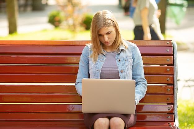 Молодой предприниматель сидит в парке и работает с ноутбуком Premium Фотографии