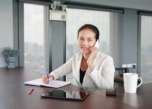 Young businesswoman sitting at the table on workplace in office using the telephone Premium Photo