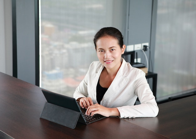 Young businesswoman sitting at the table on workplace in office with laptop computer Premium Photo