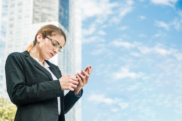 Young businesswoman standing in front of building texting message on mobile phone Free Photo