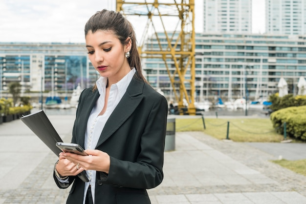 Young businesswoman standing in front of building using mobile phone Free Photo