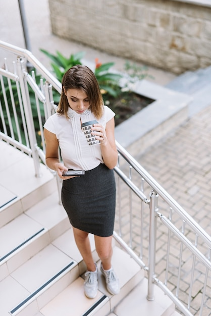 Young businesswoman standing on staircase using smartphone Free Photo