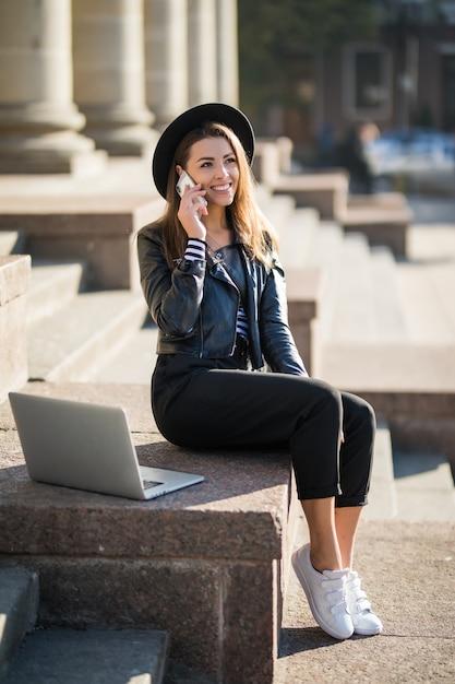 La ragazza dell'allievo della giovane donna di affari lavora con il suo computer portatile di marca nel centro urbano che si siede sulle scale di pietra nella giornata di sole Foto Gratuite