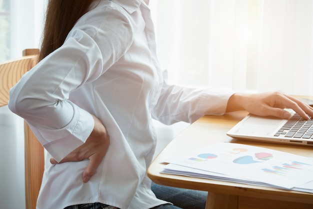 Young businesswoman suffering from backache in office Premium Photo