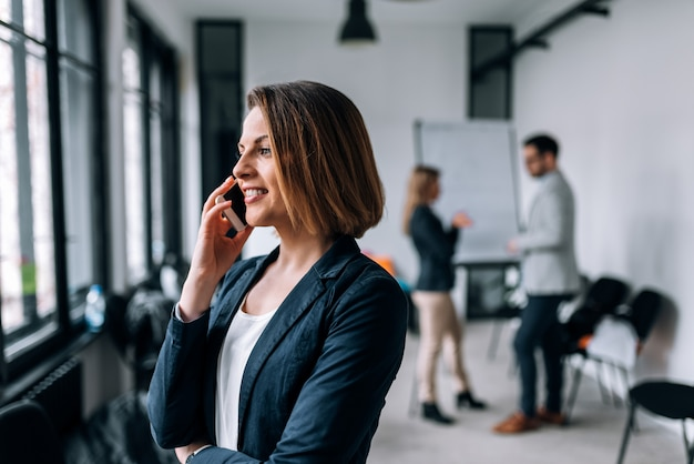 Young businesswoman talking on mobile phone with colleagues in background. Premium Photo
