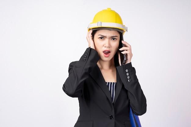 Молодой предприниматель недоволен во время разговора по мобильному телефону на белом Premium Фотографии