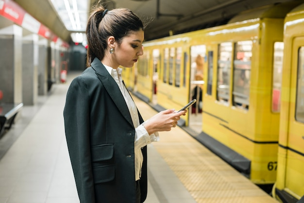 Young businesswoman using mobile phone standing at subway station Free Photo