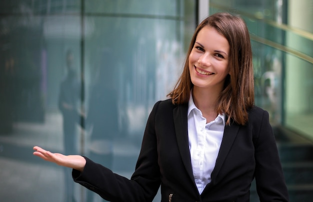 Young businesswoman welcoming you in a modern city setting Premium Photo