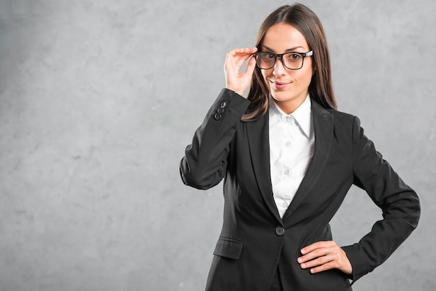 Young businesswoman with black eyeglasses standing in front of wall Free Photo