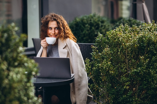 Young businesswoman working on a computer outside the cafe Free Photo