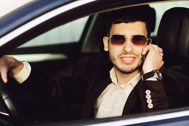 Young bussinesman in suit and black glasses speaks by phone in his car. bussines look. test drive of the new car Premium Photo
