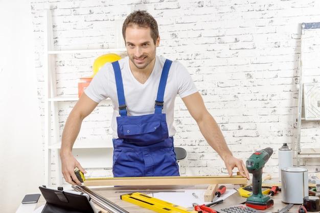 Young carpenter measuring wooden board Premium Photo
