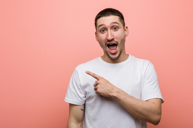Young casual man pointing to the side Premium Photo