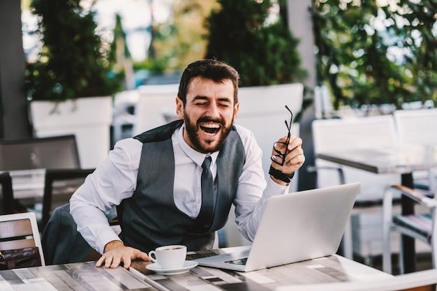 Молодой кавказский бородатый бизнесмен в костюме, сидя в кафе и смеясь над шуткой, которую он читал в интернете. перерыв на кофе. Premium Фотографии