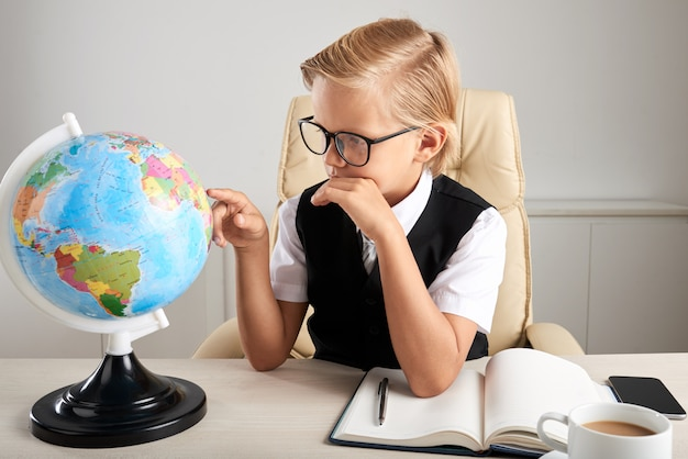 Young caucasian boy sitting in executive chair in office and looking at earth globe Free Photo