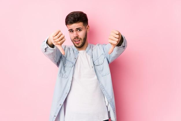 若い白人ビジネスマンが白でポーズをとって親指ダウンを示すと嫌悪感を表現します。<mixto> Premium写真