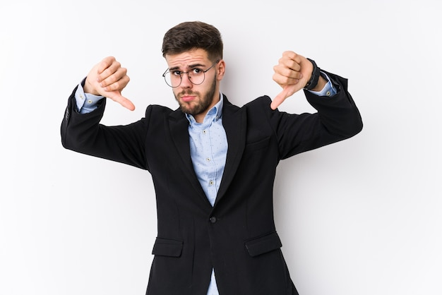 Young caucasian business man posing in a white wall isolated young caucasian business man showing thumb down and expressing dislike. Premium Photo