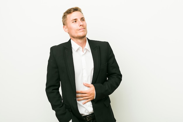 Young caucasian business man touches tummy, smiles gently, eating and satisfaction concept. Premium Photo