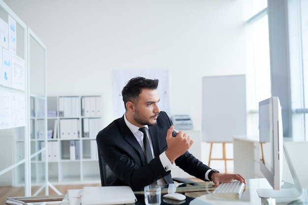 Young caucasian businessman in suit sitting in office and looking at computer screen Free Photo