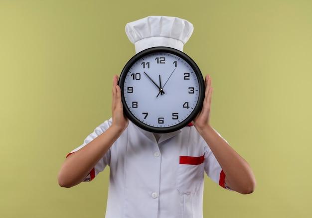 La giovane ragazza caucasica del cuoco in uniforme dello chef chiude l'orologio del woth del fronte isolato su priorità bassa verde con lo spazio della copia Foto Gratuite