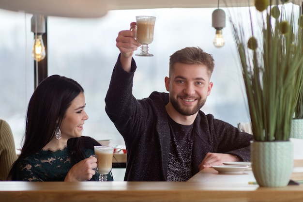 Young caucasian couple talking and drinking coffee in cafe, man greetings with mug of coffe in hand and smiling, girl laughing at that time Premium Photo