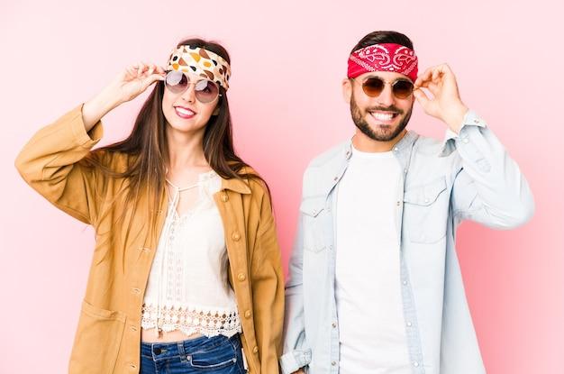Молодая кавказская пара, носящая одежду музыкального фестиваля, изолировала возбужденные, держа на глазах одобренный жест. Premium Фотографии
