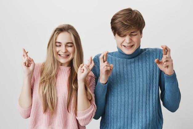 目を閉じて、顔をしかめ、灰色の空間に対してポーズをとって何かを希望する指を交差を持つ若い白人カップル 無料写真
